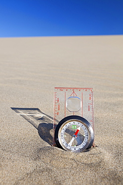 Oregon, Florence, Compass partially buried in sand