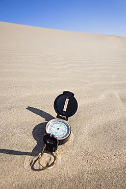 Oregon, Florence, Compass lying on sand dune