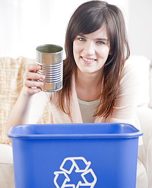 Portrait of young woman putting can in recycling bin