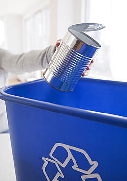Woman putting metal can into blue recycling bin