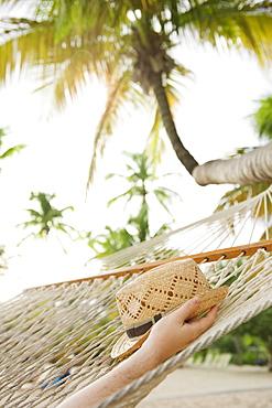 Hand holding straw hat in hammock