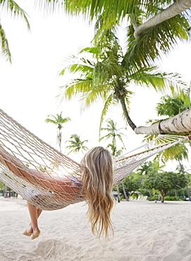 Blonde woman relaxing in hammock
