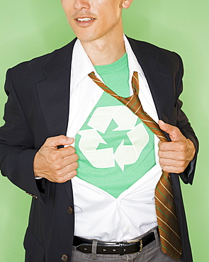 Businessman with wearing t-shirt with recycling symbol under suit, studio shot
