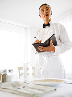 Waiter taking order and looking at camera