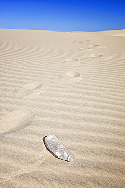 Oregon, Florence, Empty water bottle and foot prints on sand dune