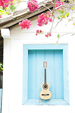 Brazil, Bahia, Trancoso, Guitar against building wall