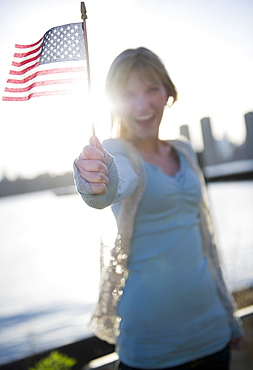 USA, Brooklyn, Williamsburg, Woman holding American flag