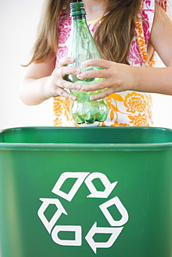Close up of girl (6-7) throwing plastic bottle to recycling bin