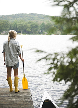 USA, New York, Putnam Valley, Roaring Brook Lake, Woman standing on pier with paddle