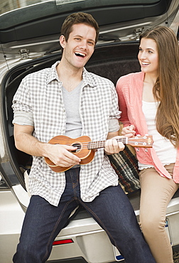 Happy young couple sitting in car boot with mandolin, USA, New Jersey, Jersey City