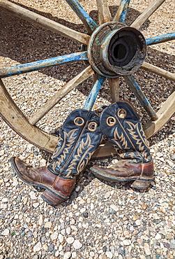 Cowboy boots against wagon wheel
