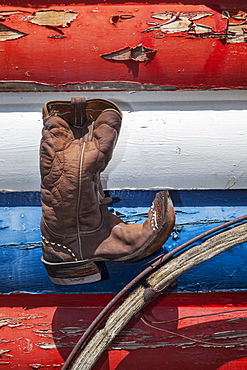Cowboy boot and wagon wheel against red, white and blue peeling paint