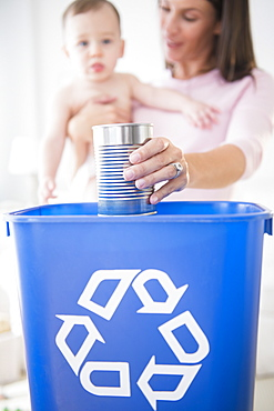 Mother and daughter (6-11 months) putting can into recycling bin