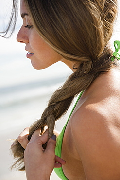 Beautiful woman braiding hair at beach