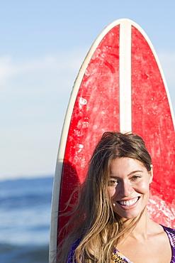 Portrait of woman with surfboard, Rockaway Beach, New York