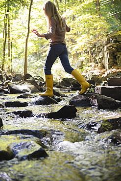 Woman walking on rocks in stream, Newtown, Connecticut