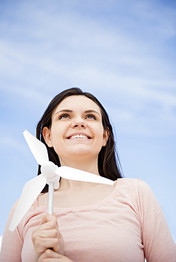 Portrait of young woman holding minature wind turbine