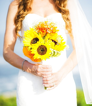 Mid section of bride holding sunflower bouquet