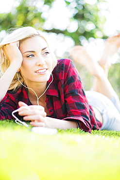 Portrait of teenage girl (16-17) lying on grass