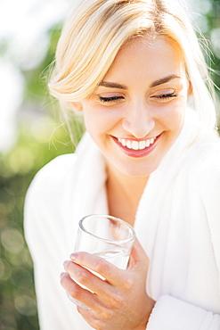 Teenage girl (16-17) wearing bathrobe drinking water
