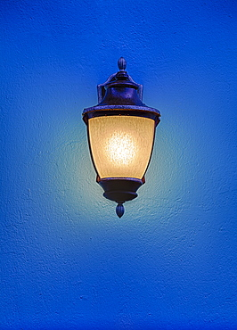 Illuminated antique street lantern floating over blue background
