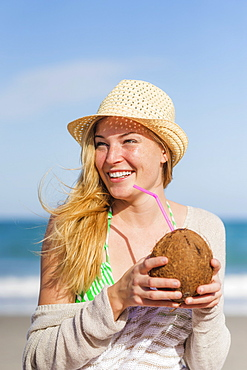 Young woman on beach drinking coconut juice, Jupiter, Florida, USA