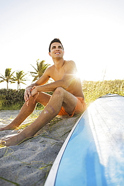 Young man sitting on beach with surfboard, Jupiter, Florida, USA