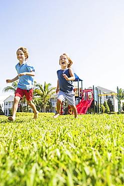 Boys (4-5, 8-9) running, Jupiter, Florida, USA