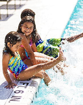 Girls(4-5, 8-9) and boy (6-7) playing on swimming pool