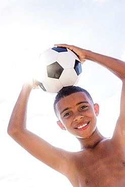 Boy (10-11) holding soccer ball on head