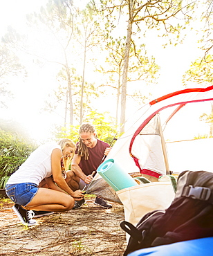 Couple setting up tent in forest, Tequesta, Florida