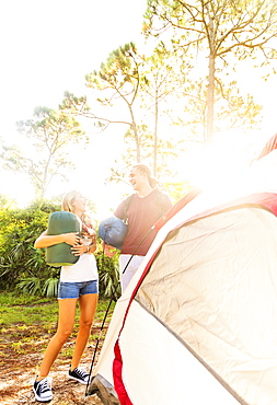 Couple standing next to tent in forest, Tequesta, Florida