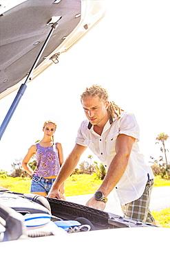 Couple checking car engine, Tequesta, Florida