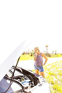 Woman looking at car engine, Tequesta, Florida