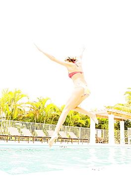 Woman jumping into swimming pool, Jupiter, Florida