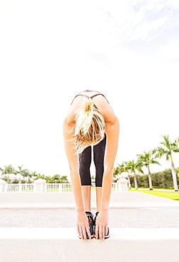 Woman reaching for toes, Jupiter, Florida
