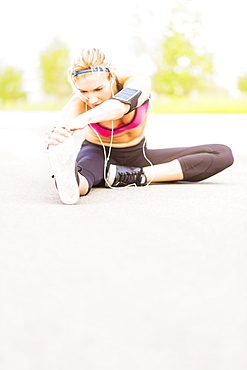 Young woman listening to music while stretching, Jupiter, Florida