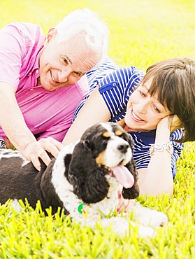 Smiling couple with dog lying in grass