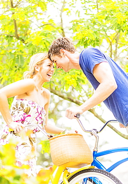 Portrait of young couple sitting on bicycles, touching foreheads, laughing, Jupiter, Florida