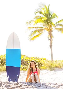 Portrait of young woman sitting near surfboard on beach, Jupiter, Florida