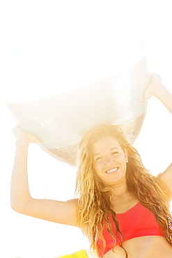 Portrait of young woman holding surfboard over head, Jupiter, Florida
