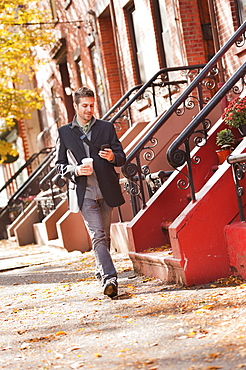 Man walking with mobile phone and coffee