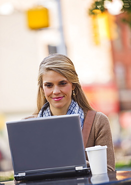 Young woman sitting with laptop in sidewalk cafe