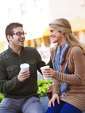 Young couple sitting with take-away coffee