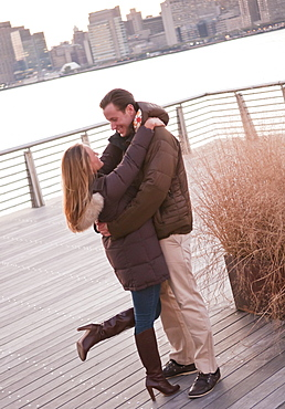 USA, New York, Long Island City, Young couple embracing on boardwalk