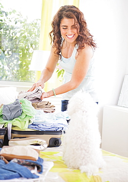 Smiling woman packing suitcase with dog