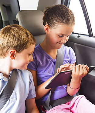 Boy (6-7) and girl (8-9) using digital tablet while sitting in car