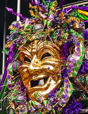 Mardi Gras mask hanging on balcony's railing