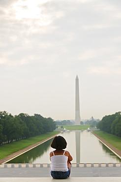USA, Washington DC, girl (6-7) looking at Washington Monument