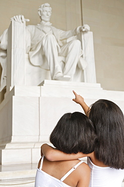 USA, Washington DC, Lincoln Memorial, two girls (10-11] looking at Lincoln statue